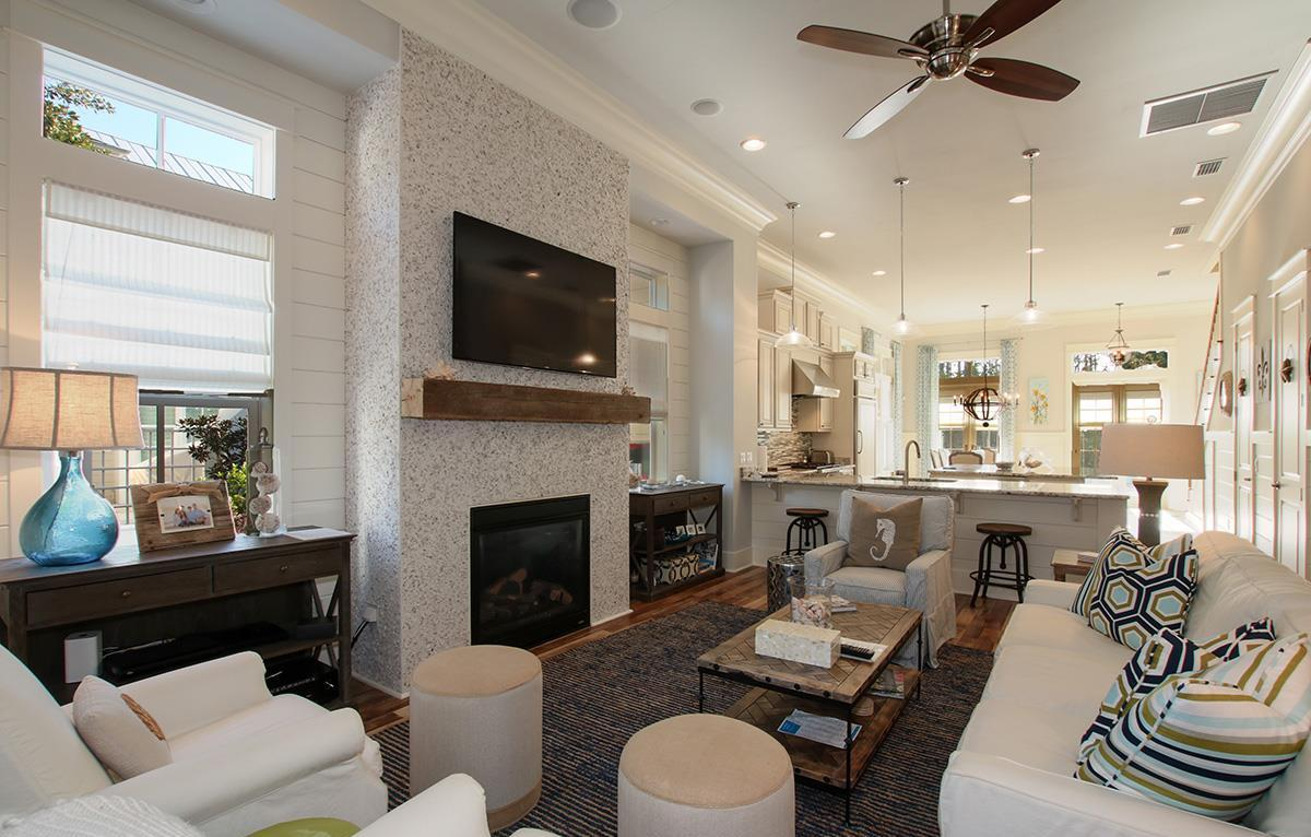Open- concept living space with gorgeous fireplace, mounted TV, and seating for all.