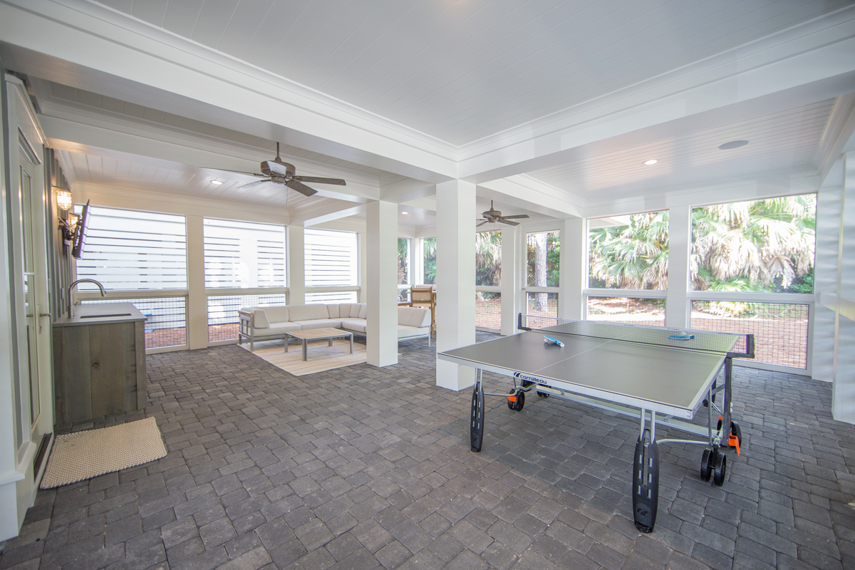 Amazing screened in area on 1st floor with ping pong and outdoor sofa and high top card table