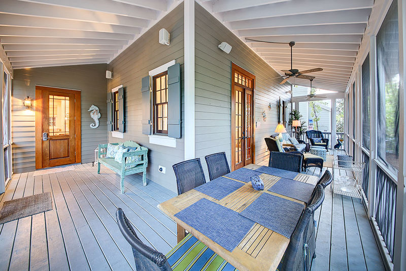 The back porch is screened in and has a dining table and conversational seating