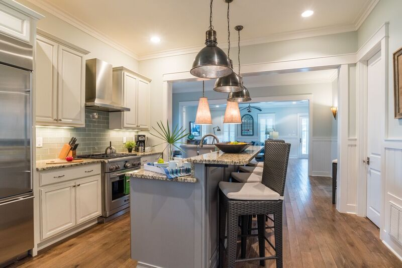 Open kitchen with stainless steel appliances, a large gas range and bar seating for 4