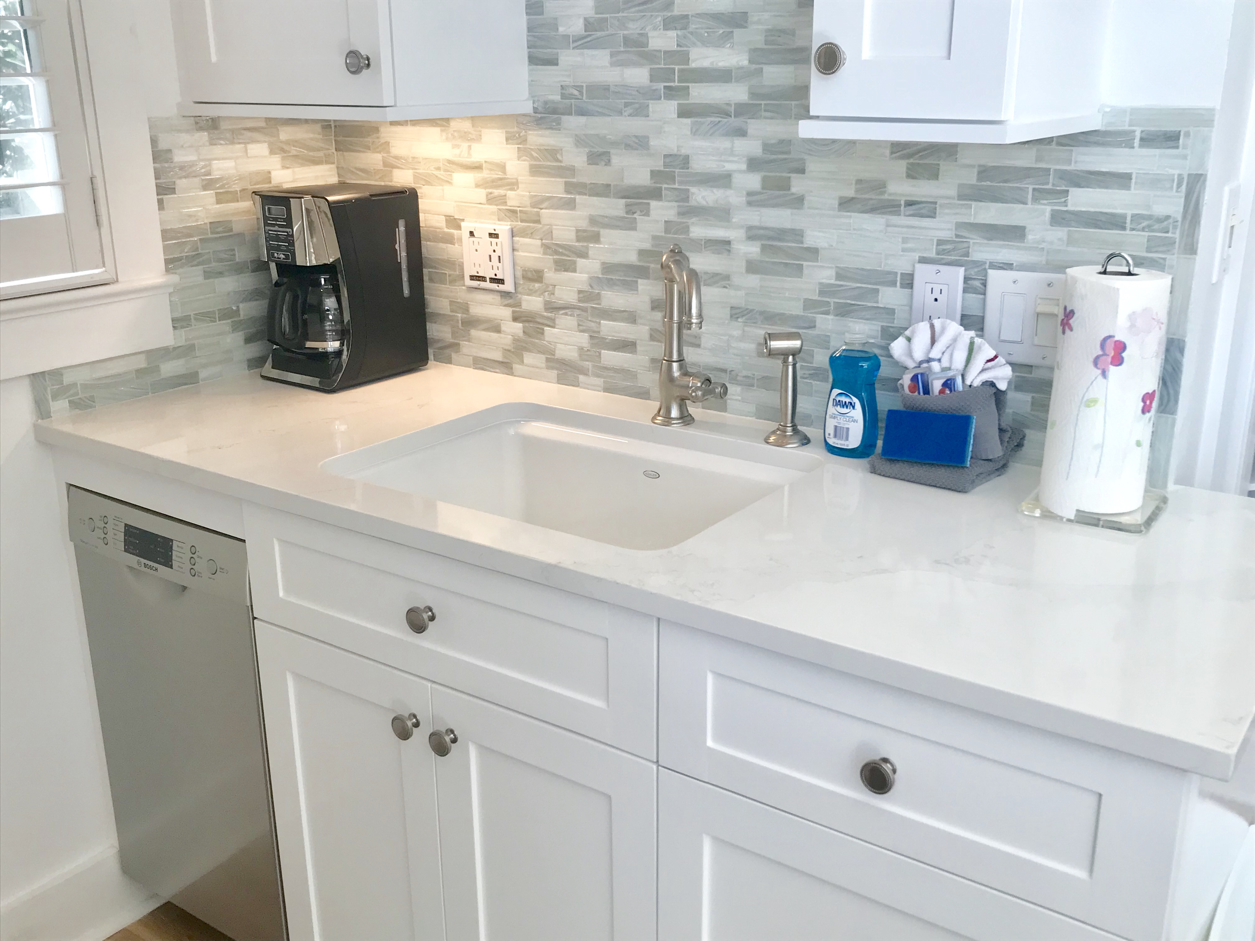 Gorgeous counters a modern backsplash highlight the updates in the kitchen