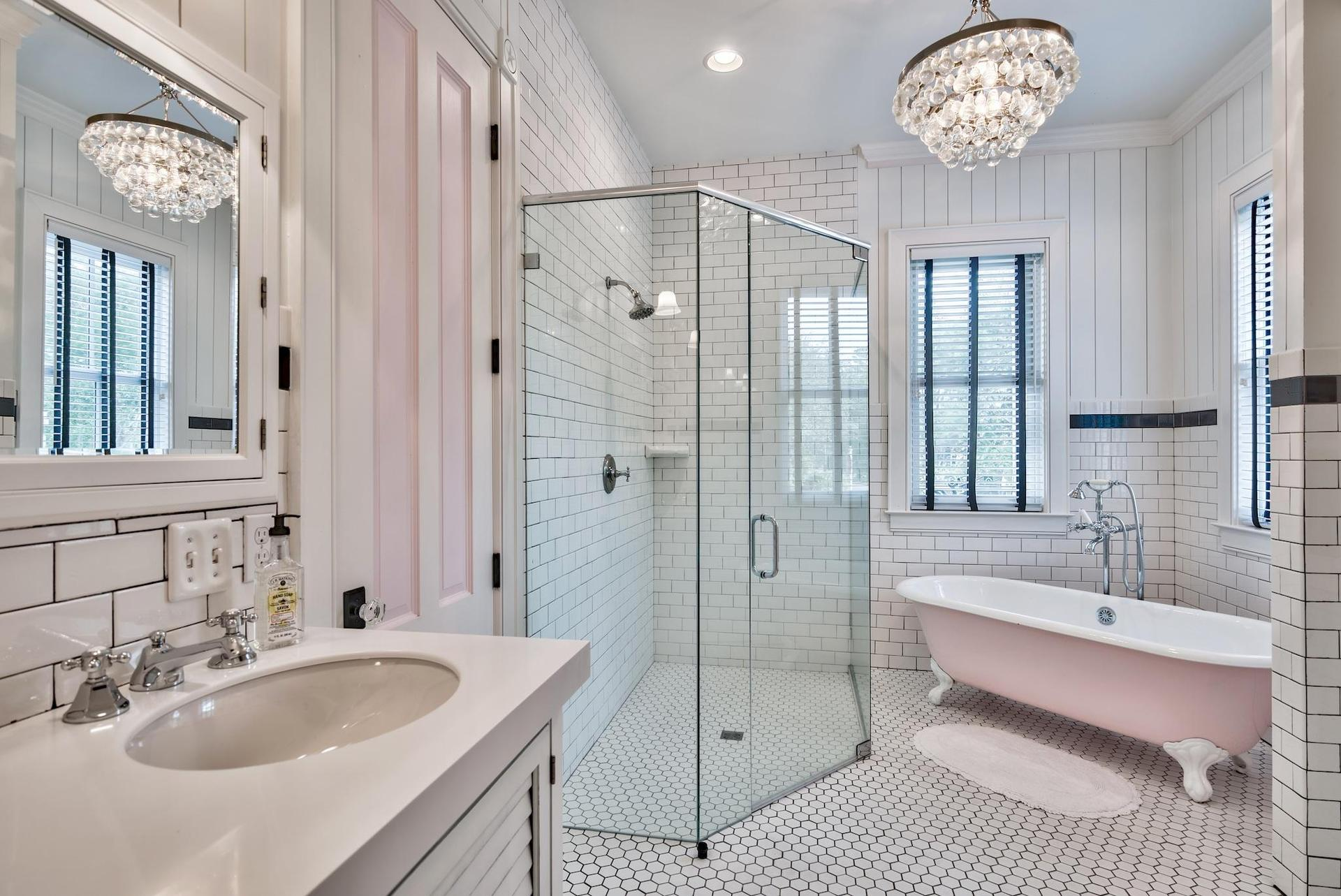 Master bath with a claw foot tub and crystal chandelier