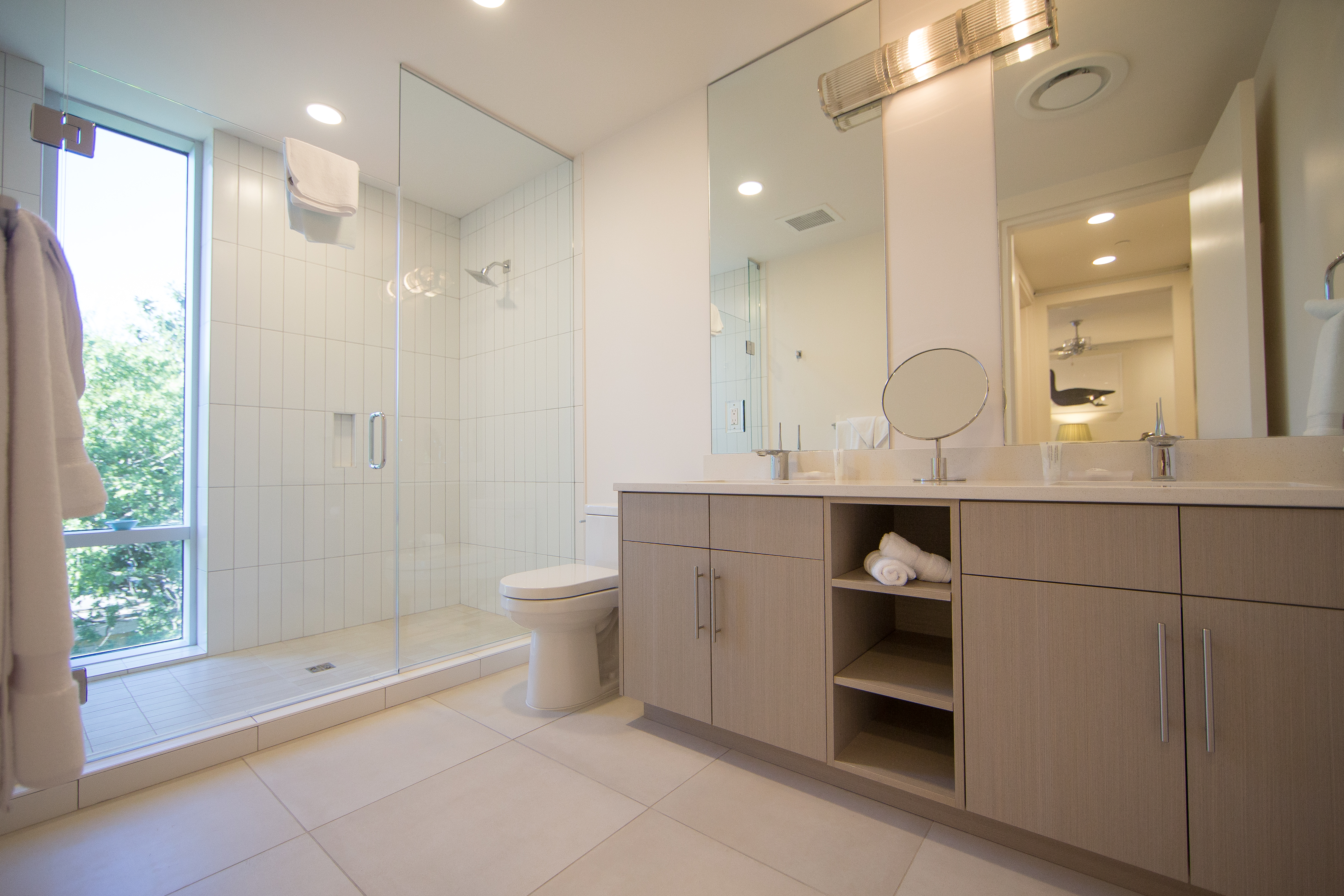 Double queen guest bathroom with a walk in shower
