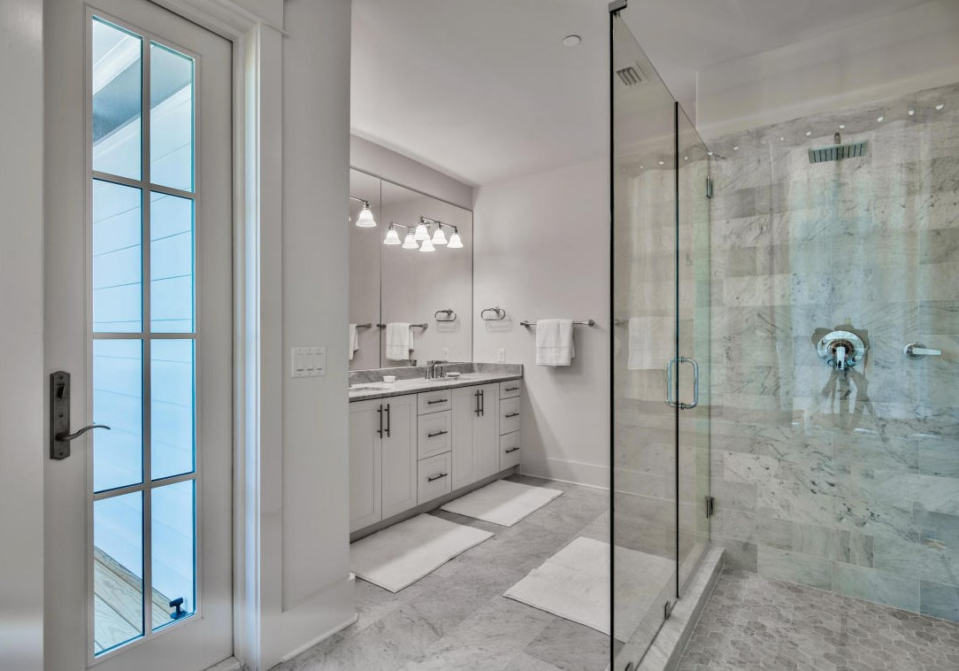 Beautiful stone counters and marble tile accent the master bath