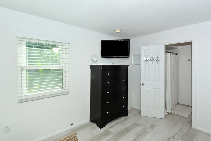 Master bedroom with ensuite bathroom and flat screen TV.