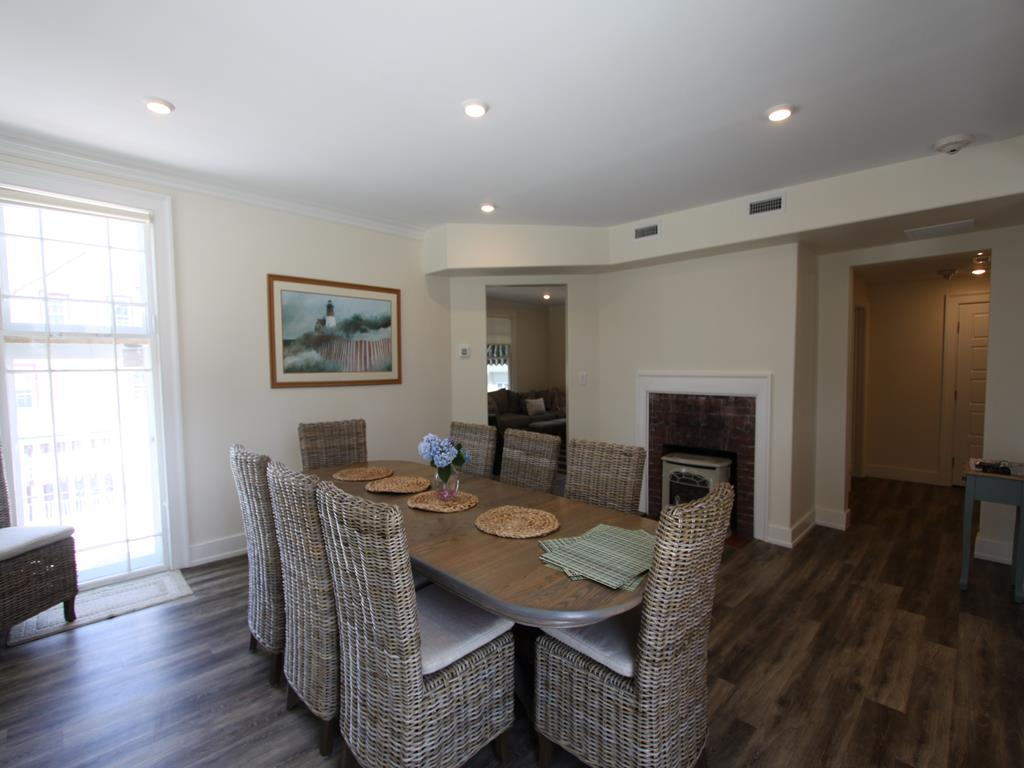 View of dining area with gas fireplace and doorway into living/family area