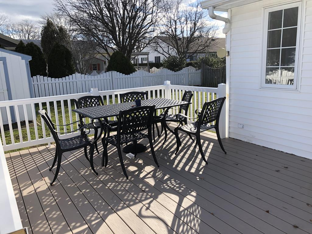 Outdoor dining/entertainment on the deck with overlooks the fenced in yard