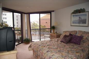 Spacious bedroom has double doors leading to private porch