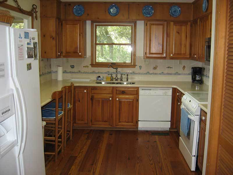Kitchen has counter with chairs facing a pass through to screened in porch