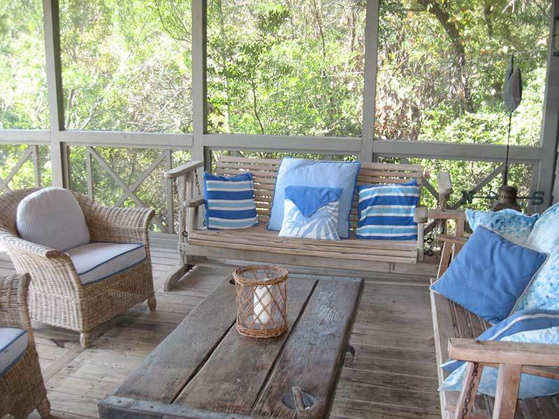 Screened in porch facing beach with table & chairs