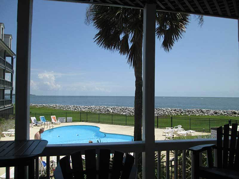 View of pool and ocean from the  balcony which has a pub size  table and chairs