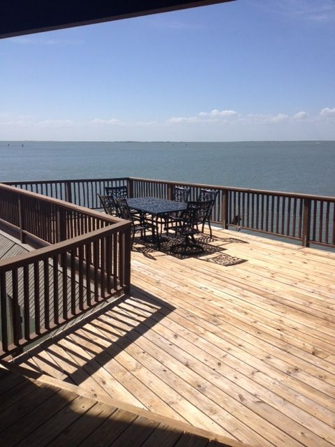 Large upper deck with table and chairs over the water.