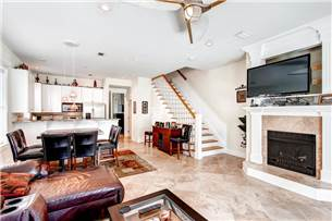 Living area with large flat screen TV and decorative fireplace