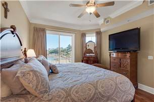 Master bedroom with balcony access and pool view