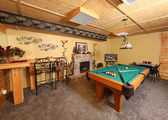 Game room with pool table, games table and flat screen TV.