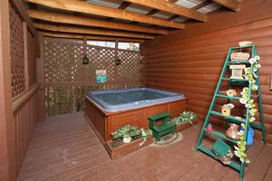 Hot tub with privacy barrier on deck.