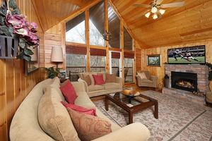 Main room with seating, fireplace, flat screen TV and pool table.