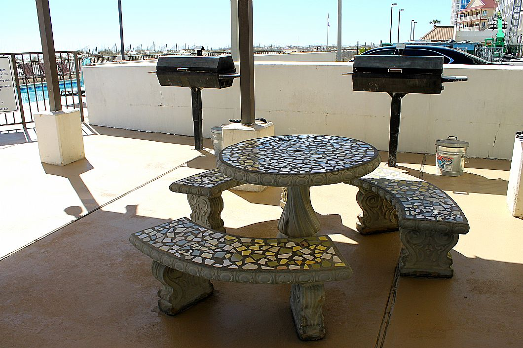 Grill area w/ picnic tables by the pool