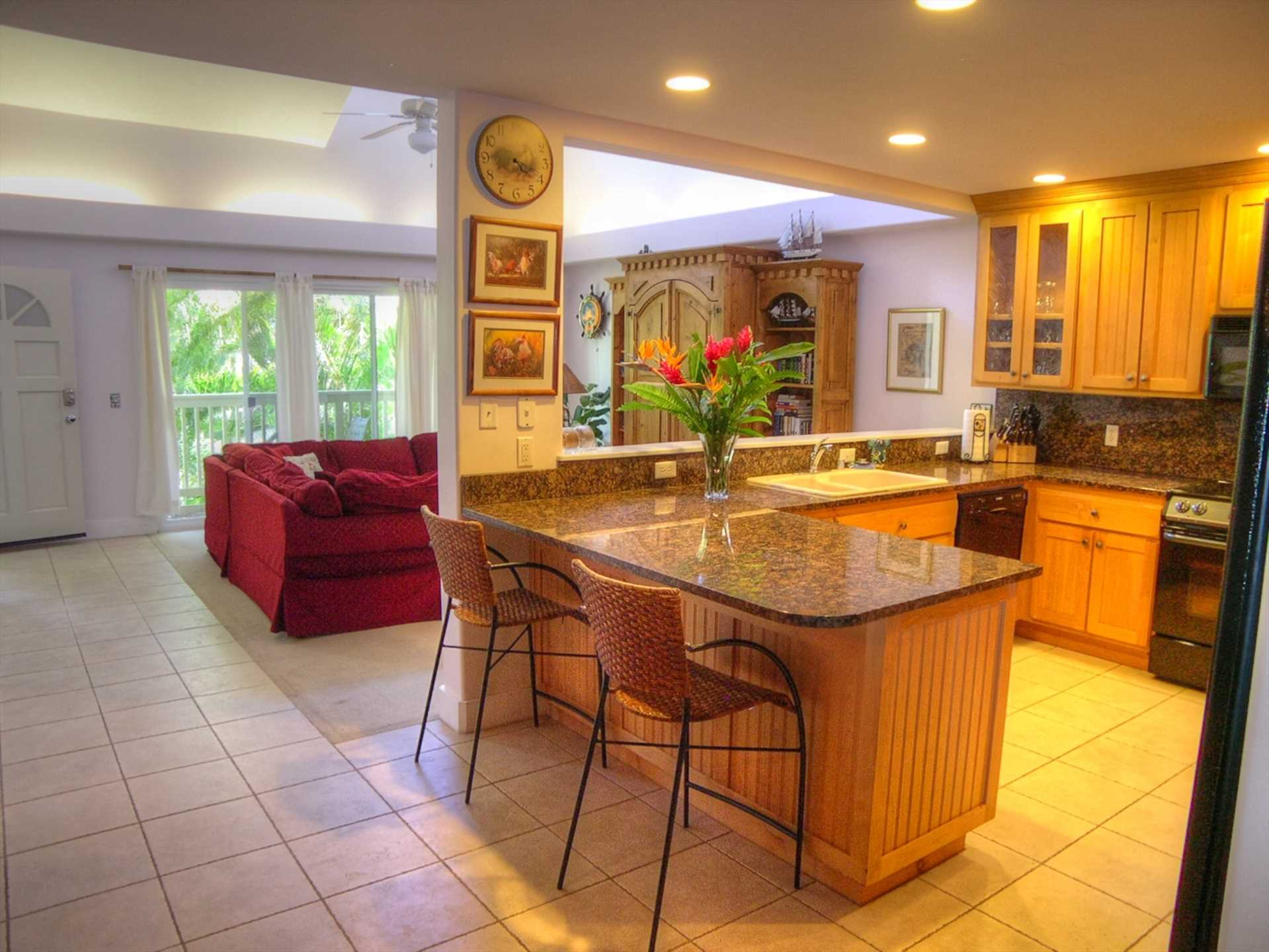 Granite and travertine tile kitchen opens to dining room and living room
