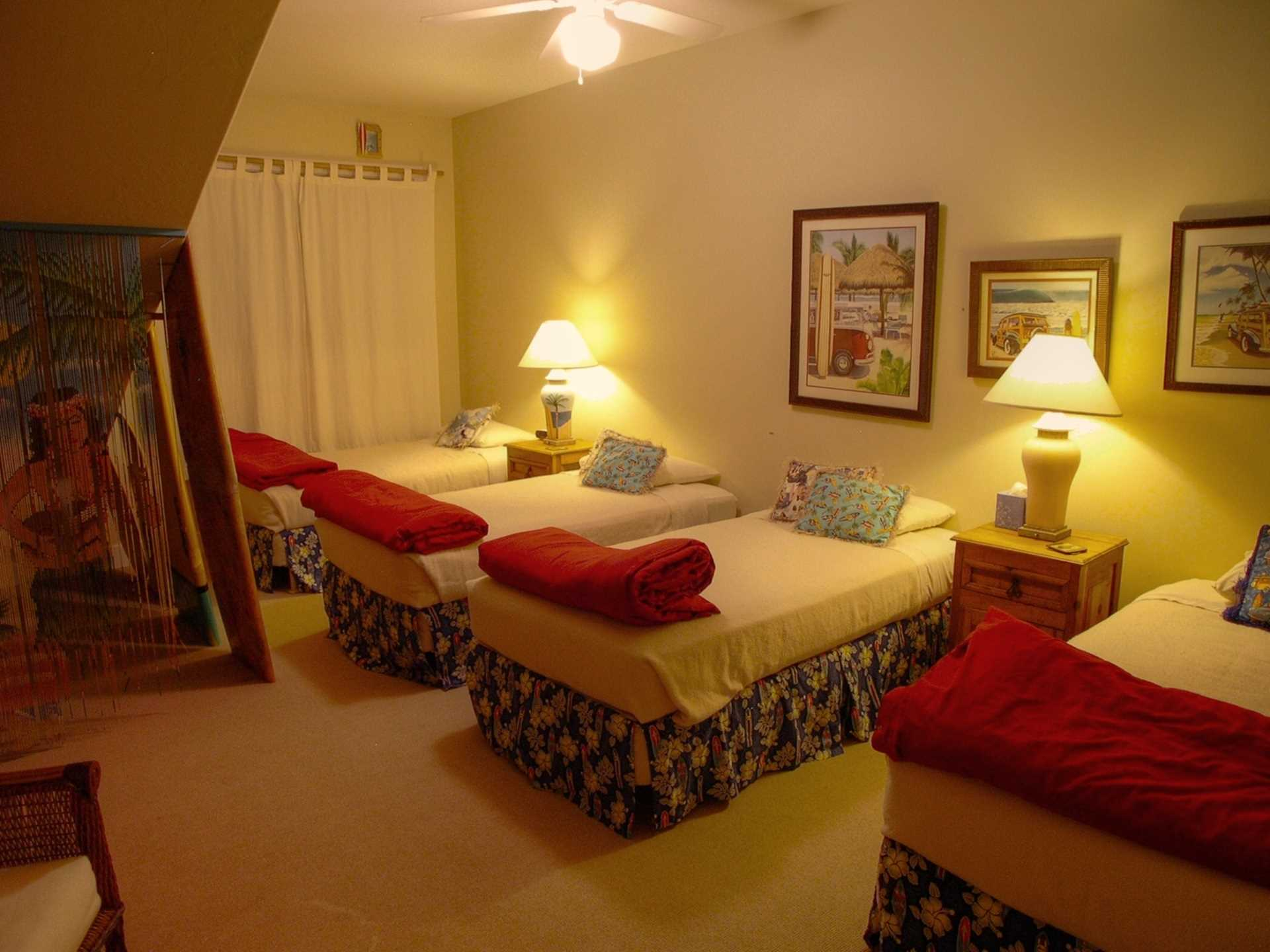 The Surfer's Bedroom is colorfully decorated with surf boards and fun pictures.  It features four twin beds and a TV so the kids can disappear while the adults enjoy conversation in the living room.