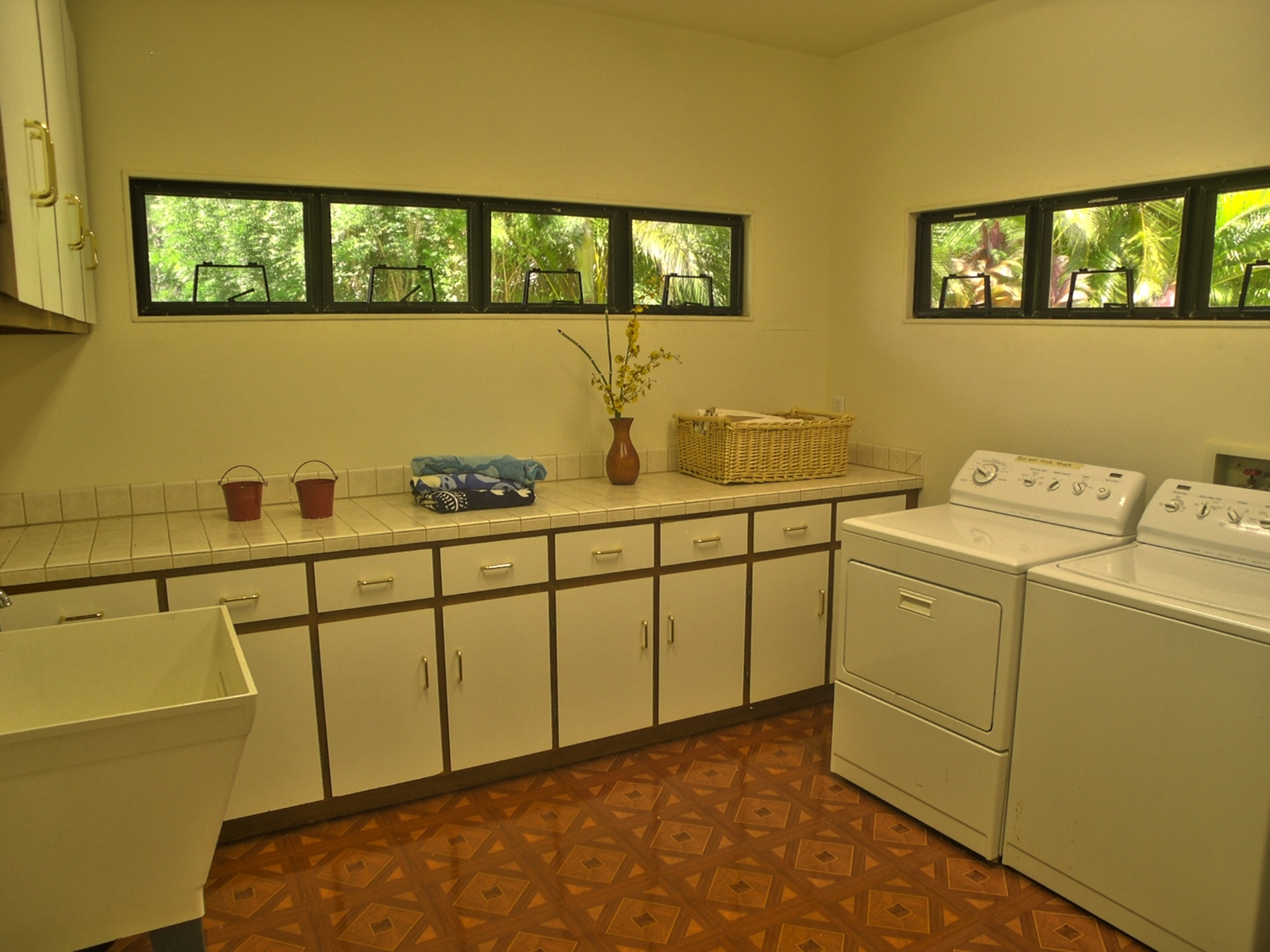 Large laundry room with counter space and ironing board.