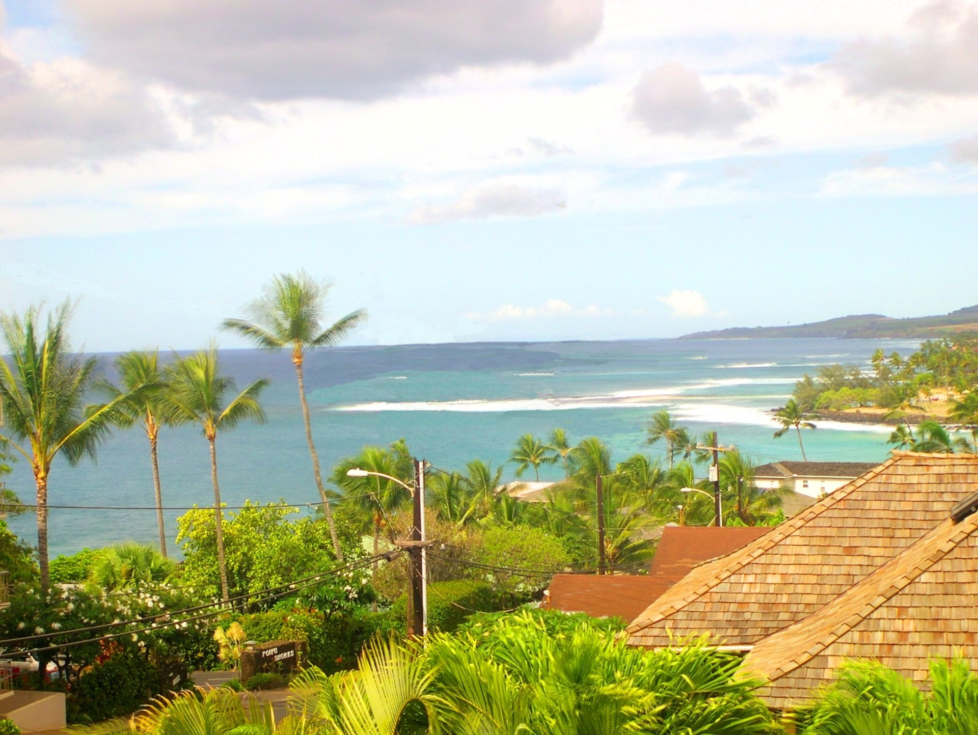 The home is located on a rise overlooking Kauai's southern coastline.  This view from the upper deck shows Brennecke beach in the foreground and Poipu Beach where the land juts out into the ocean