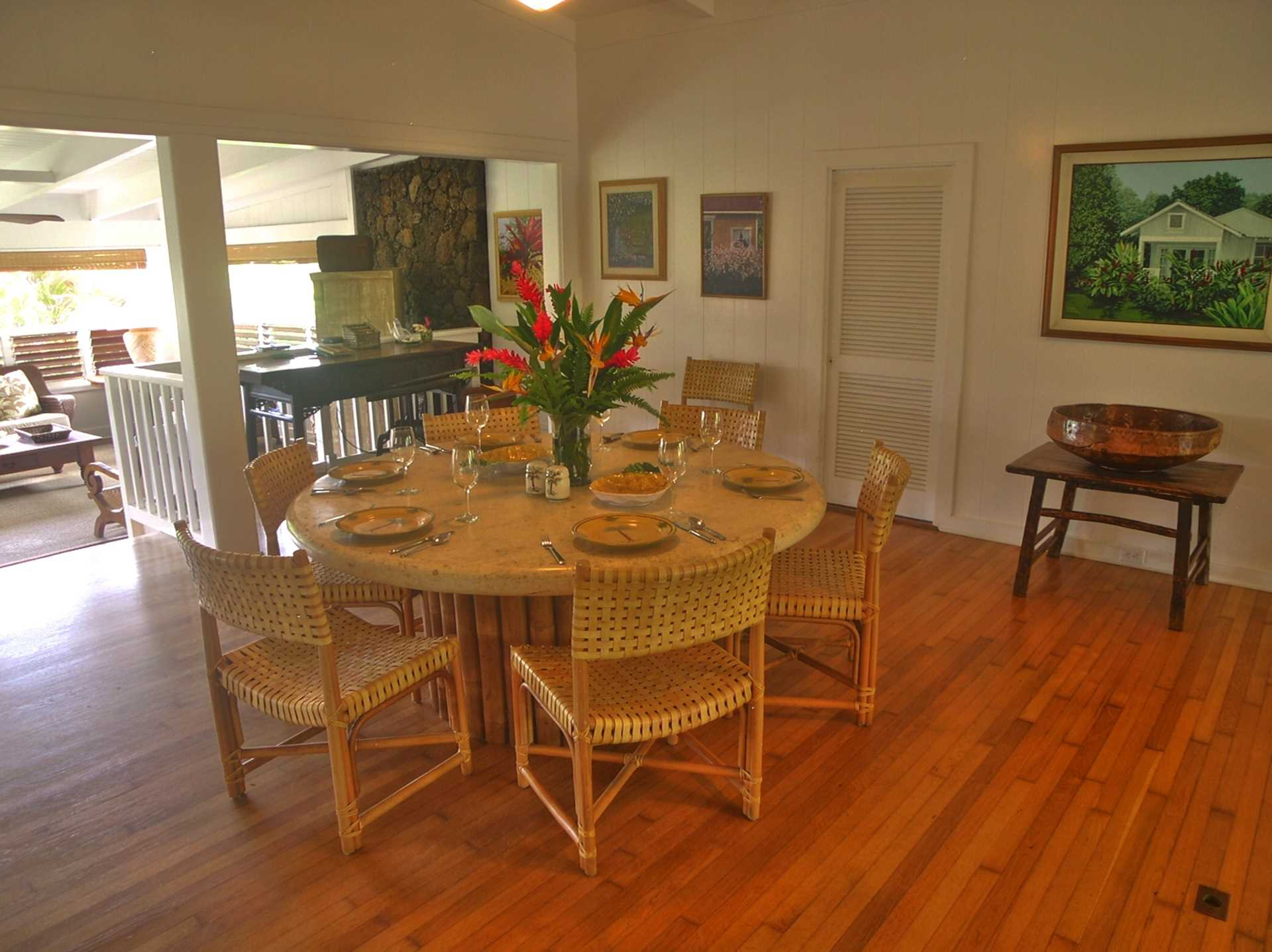 A huge round dining table and vintage oak floors presents a spacious open floor plan leading to the sitting area, family area, and wide double sliding doors to the lovely covered lanai.
