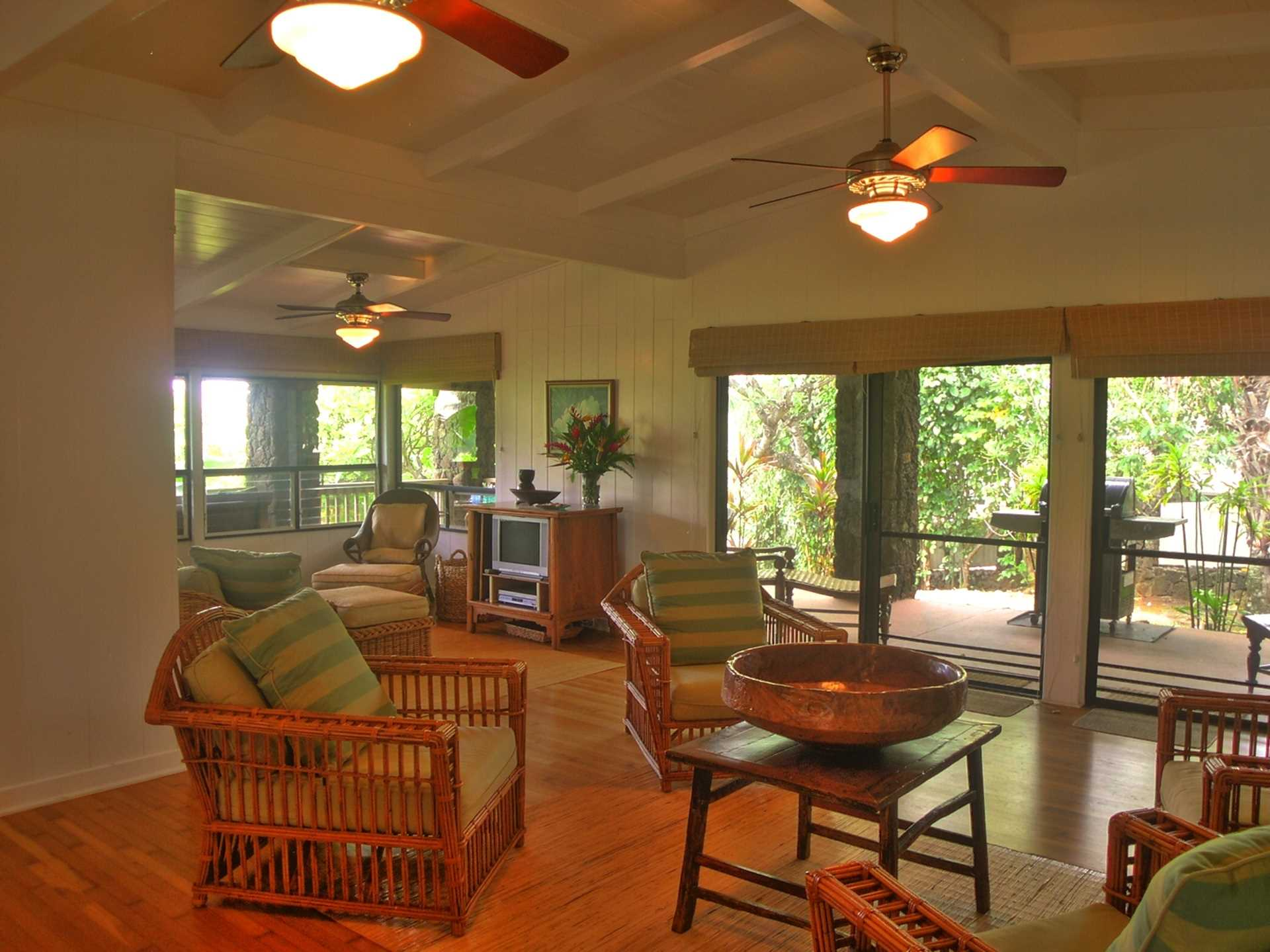 Photo showing sitting area in front of fireplace with family room off to the left.  Double sliding doors to lanai open to invite in the delighful island breezes.