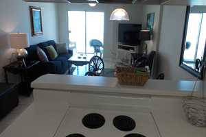 Kitchen facing living area - large, flat-screen television in the living area with balcony access!