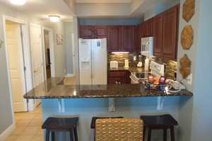 With bar stools, sit and watch the cook whip up a meal in the kitchen at this Crystal Towers condo