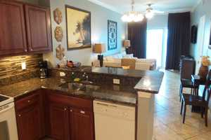 Beautifully laid out two bedroom condo - kitchen with dining and living area in background with balcony access!
