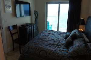 King-size bed, flat-screen television and balcony access in the master bedroom suite
