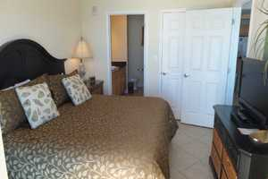 King-size bed in the master bedroom with attached bathroom and flat-screen television