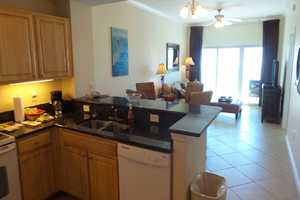 Kitchen facing living area and balcony - plenty of places to sit and relax in the condo during your stay!