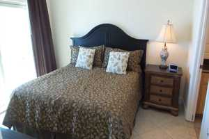 Master bedroom suite with king-size bed, flat-screen television, attached bathroom and balcony access
