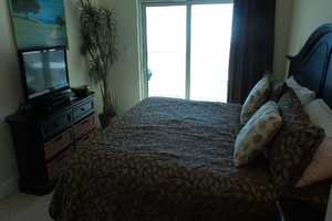 Master bedroom suite with king-size bed, flat-screen television and balcony access