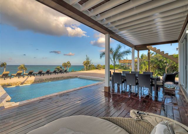 The ocean view deck features an outdoor dining table for 8, chaise lounges, and a round day bed for two.