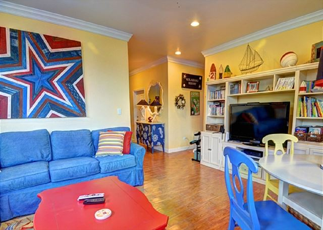 Extra large family room with books, games, and 60-inch flat-screen TV