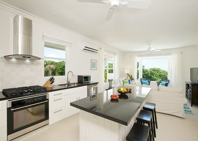 Modern island kitchen finished with black granite and stainless steel.