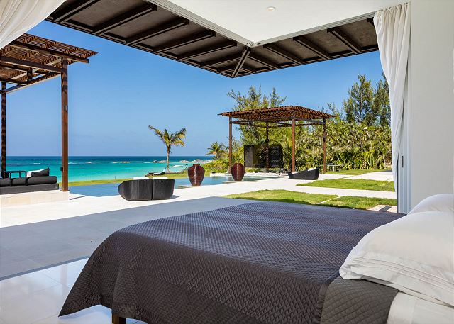 Pavilion bedroom suite with pool and ocean view and retractable glass wall.