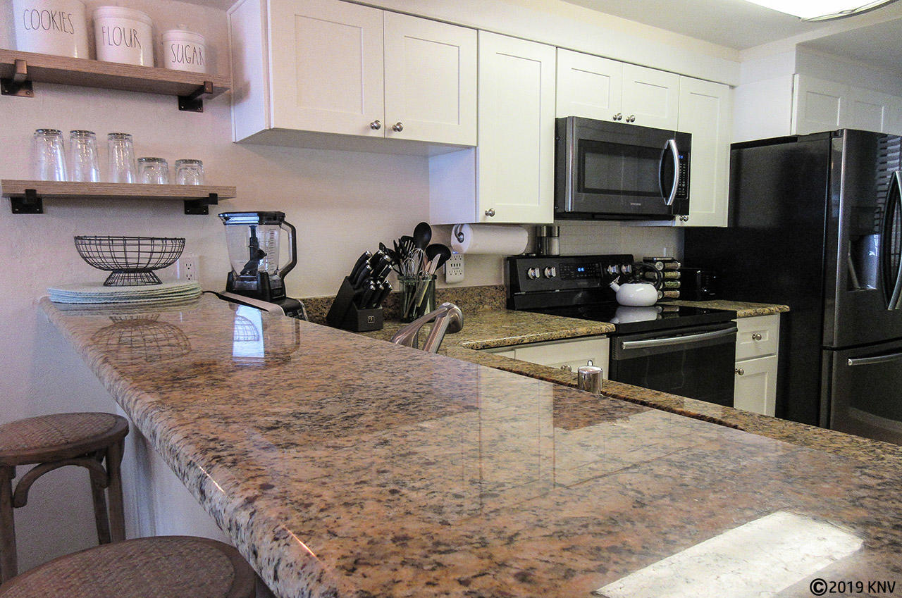 Fully equipped kitchen features granite countertops and a beautiful design.