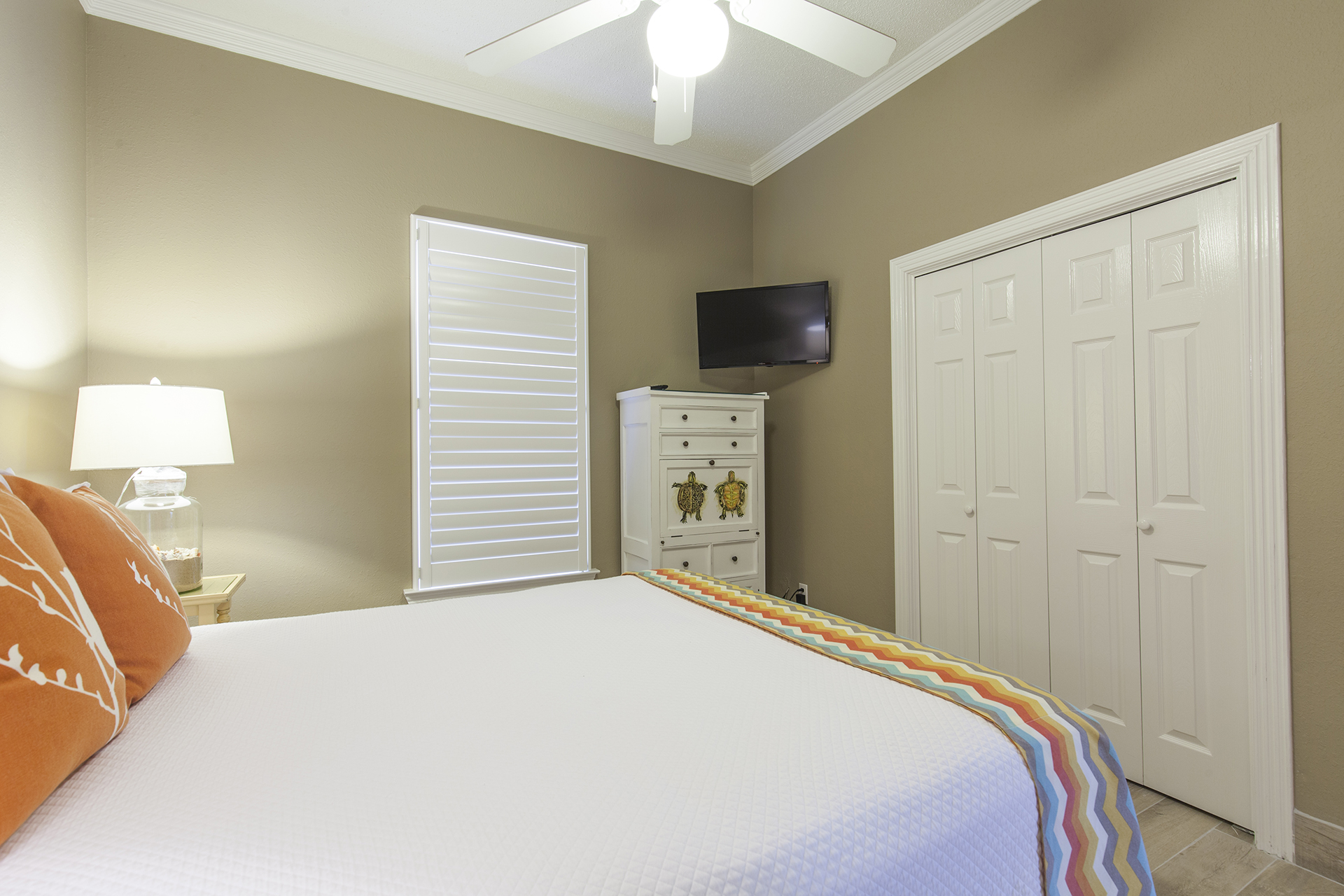 Guest bedroom with flat screen TV and additional closet storage