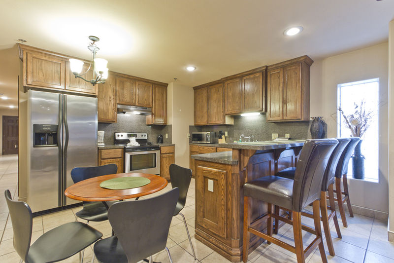 Condo # 2, kitchen and dining area with additional bar seating and stainless steel appliances