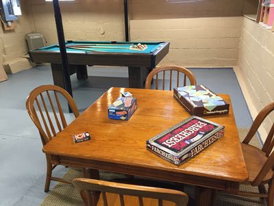 There is a pool table in the basement and a game table.  There are many games, puzzles and cards.