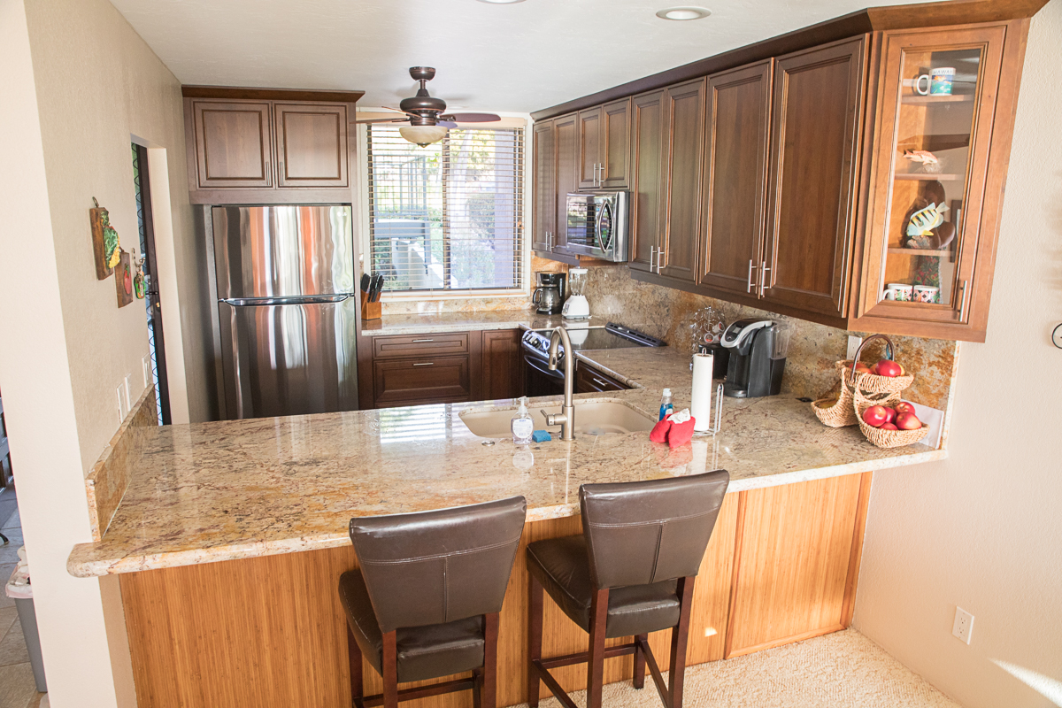 Full kitchen with view out to the lanai, golf course  and ocean beyond.