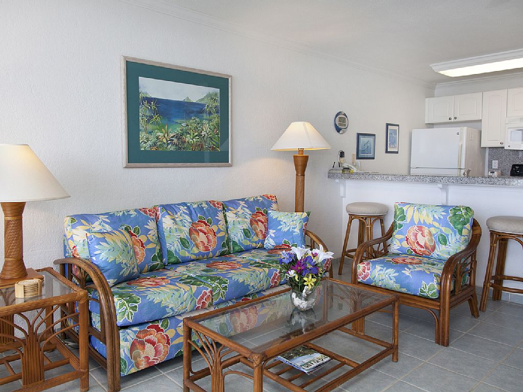 Living room offers in condo table and chairs and cable TV.