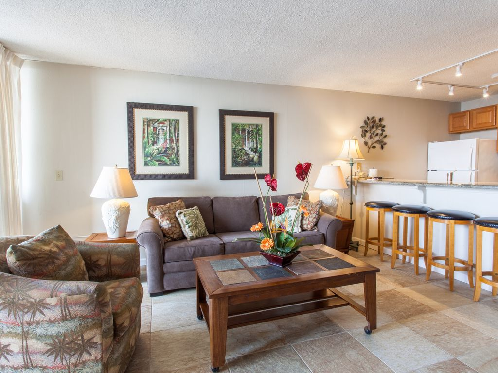 Comfortable living room with an open floor plan to the kitchen and lanai.