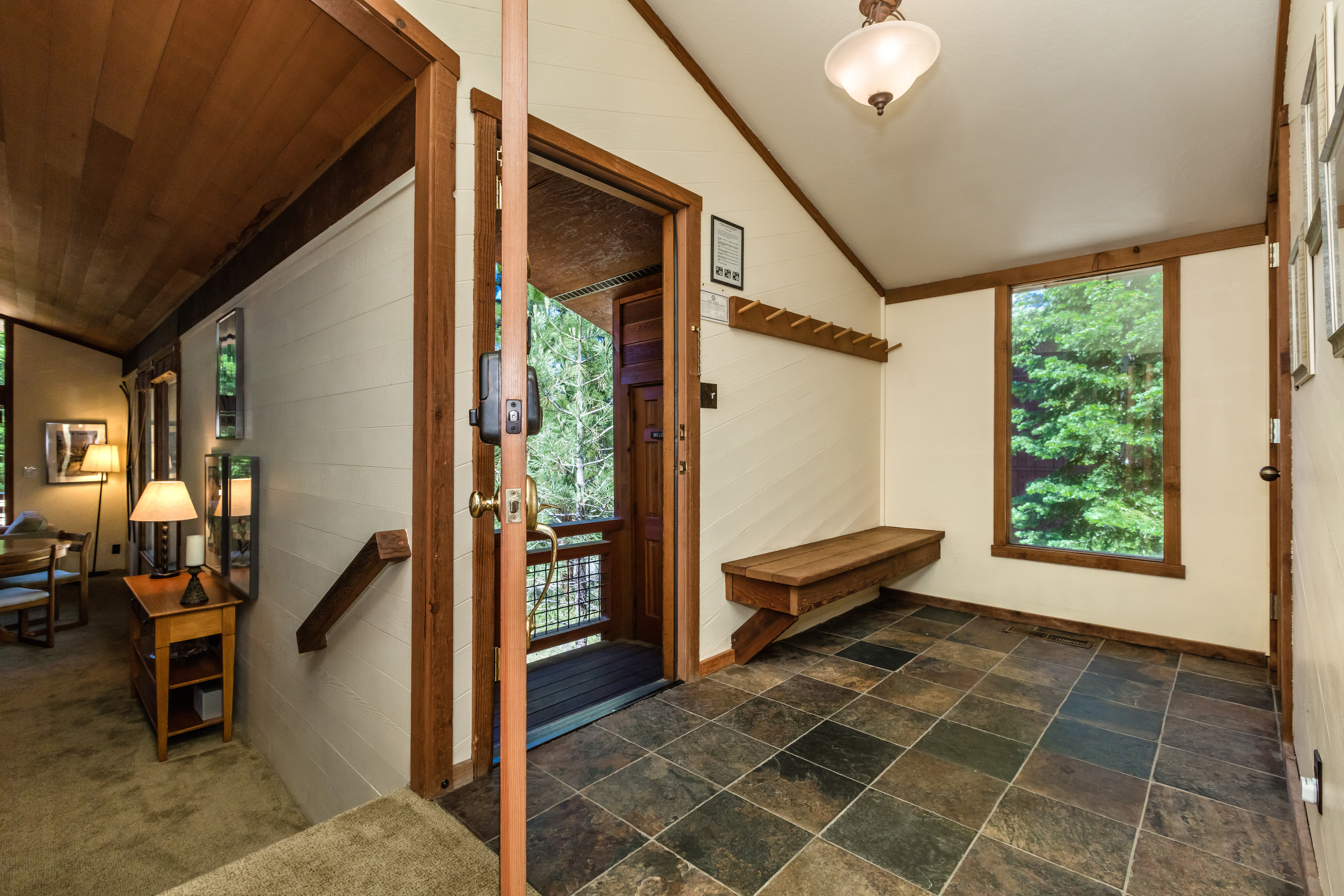 Enter up the stairs through the stone foyer-equipped w/bench and coat racks