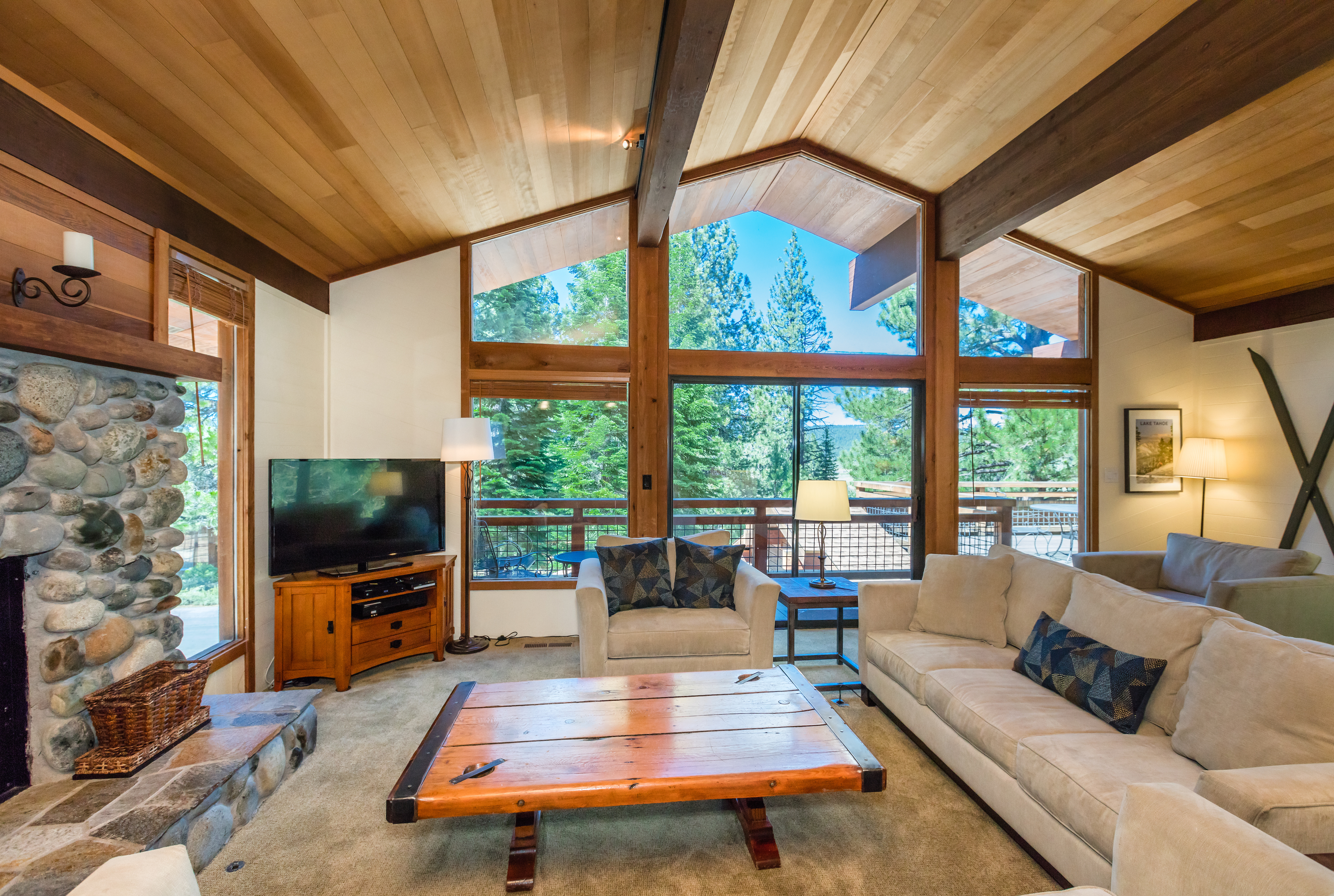 Pine tree views from the great room, sliders open to a front deck with outdoor seating