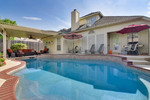 Backyard Pool with Tanning Ledge,  Covered Patio, Lounging chairs, Bluetooth Speakers, Grill, and Privacy fence.